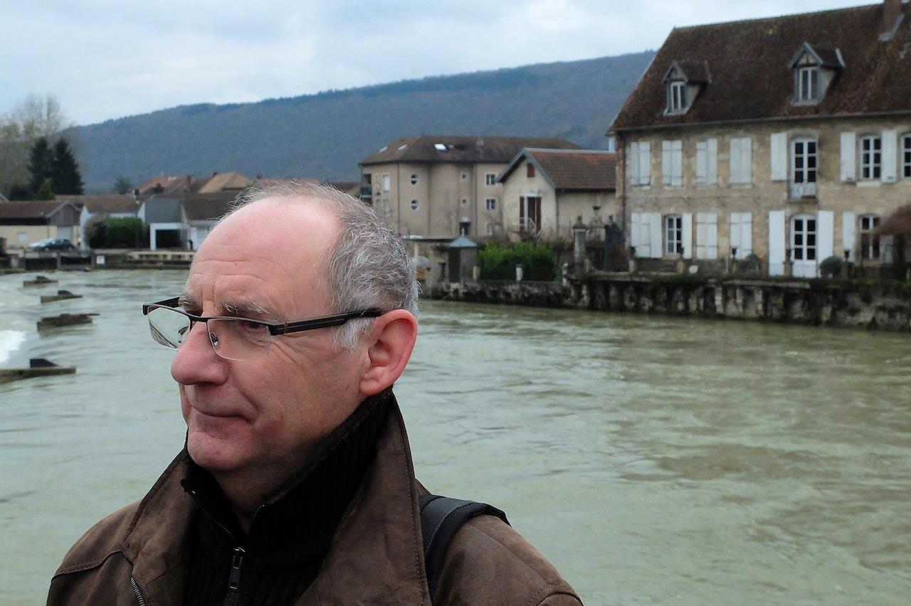 « Ce n'est pas l'éolien qui supprimera le nucléaire », dit Jean-Luc Bertron, sur le pont de la Loue à Quingey. Dans le fond, la crête de Moimi où six éoliennes pourraient être implantées. Ph D.B.