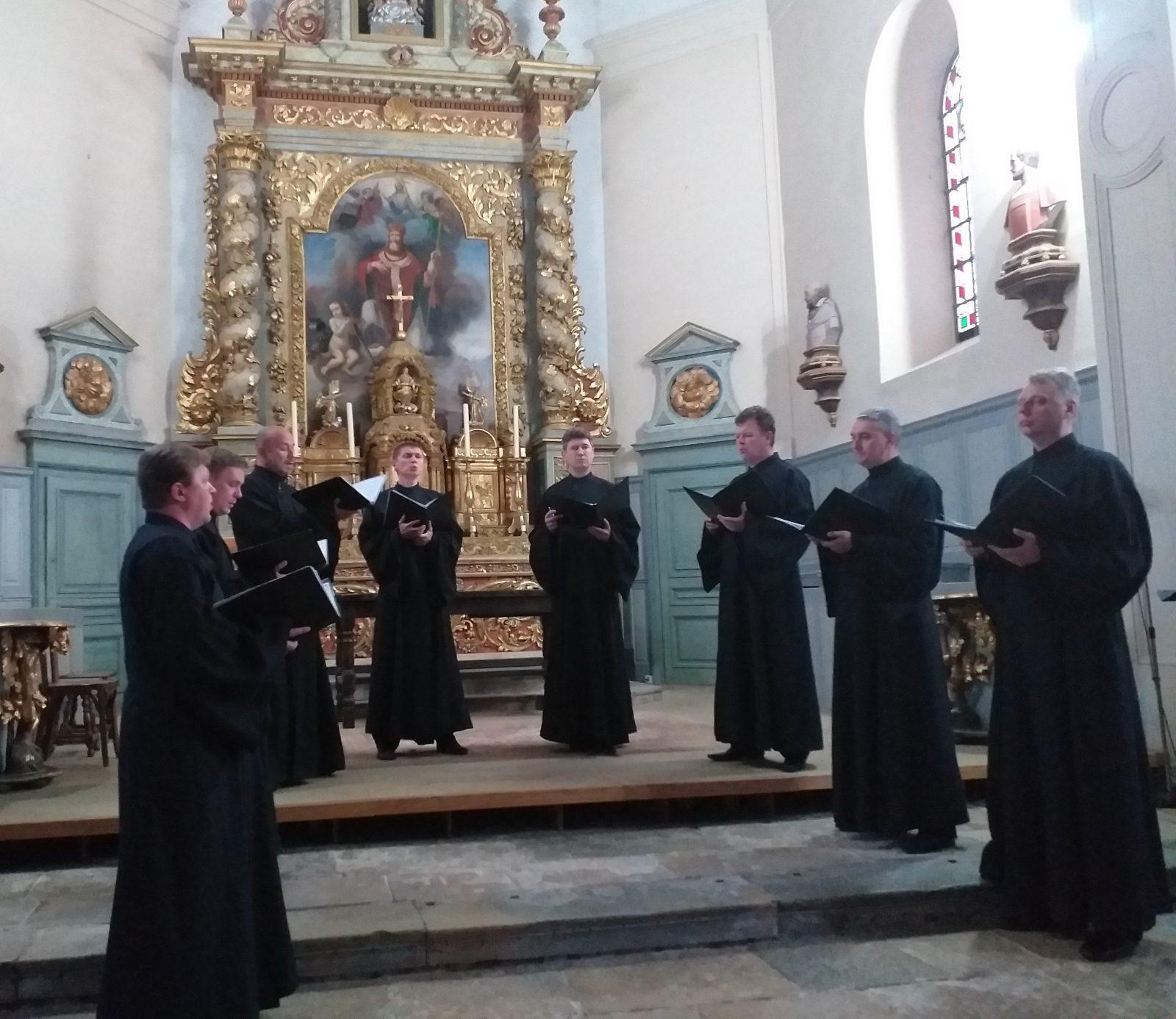 Les hommes en chasubles noires interprètent des chants de la liturgie orthodoxe.